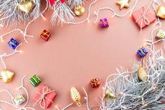 Το ζωηρόχρωμο υπόβαθρο Χριστουγέννων με τους κώνους κωνοφόρων, snowflakes, παρουσιάζει και Χριστουγέννων φω'τα σε ένα θερμό υπόβα Στοκ Φωτογραφίες