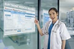 Το ηλεκτρονικό σύστημα ιατρικών αναφορών παρουσιάζει στη διαφανή επίδειξη επάνω στοκ εικόνες με δικαίωμα ελεύθερης χρήσης