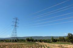 Το ηλεκτροφόρο καλώδιο περνά τον τρόπο στο αγρόκτημα στην Ταϊλάνδη στοκ εικόνα