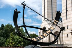 Το ηλιακό ρολόι μετάλλων ή το ηλιακό ρολόι με τους ρωμαϊκούς αριθμούς σταθμεύει δημόσια και ενσωματώνοντας το υπόβαθρο Στοκ Εικόνες