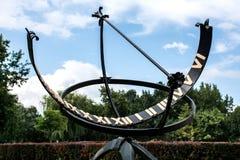 Το ηλιακό ρολόι μετάλλων ή το ηλιακό ρολόι με τους ρωμαϊκούς αριθμούς σταθμεύει δημόσια Στοκ εικόνα με δικαίωμα ελεύθερης χρήσης