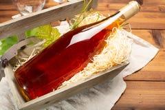 Το ηλικίας άσπρο κρασί, καθιερώνον τη μόδα πορτοκαλί κρασί στο μπουκάλι εξυπηρέτησε στο παλαιό ξύλο Στοκ φωτογραφία με δικαίωμα ελεύθερης χρήσης