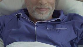 Το ηλικίας αρσενικό που βρίσκεται στο κρεβάτι και που τεντώνει, ικανοποιημένο άτομο που ξυπνά, κλείνει τη τοπ άποψη φιλμ μικρού μήκους