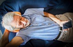 Το ηλικιωμένο άτομο ακούει μουσική με το ακουστικό στον καναπέ στοκ φωτογραφίες με δικαίωμα ελεύθερης χρήσης