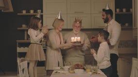 Το ηλικιωμένο άτομο εκρήγνυται τα κεριά στο κέικ απόθεμα βίντεο
