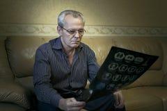 Το ηλικιωμένο άτομο εξετάζει τις εικόνες στοκ φωτογραφία με δικαίωμα ελεύθερης χρήσης