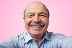 Το ηλικιωμένο ανώτερο άτομο με ένα mustache που κρατά ένα smartphone και κάνει selfie στοκ φωτογραφία με δικαίωμα ελεύθερης χρήσης