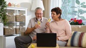 Το ηλικιωμένο ζεύγος σύνδεσε με τους φίλους χρησιμοποιώντας την τηλεοπτική κάμερα και την κατανάλωση CHAMPAGNE κλήσης lap-top απόθεμα βίντεο