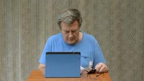 Το ηλικιωμένο πρόσωπο προσπαθεί να κάνει μια αγορά στο διαδίκτυο χρησιμοποιώντας μια ταμπλέτα και μια πιστωτική κάρτα απόθεμα βίντεο
