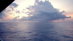Το ηλιοβασίλεμα, θάλασσα, ο ήλιος καλύπτεται με τα σύννεφα Ανοικτή ωκεάνια άποψη απόθεμα βίντεο