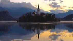 Το ηλιοβασίλεμα πέρα από τη λίμνη αιμορράγησε με την εκκλησία του ST Marys της υπόθεσης στο μικρό νησί  Αιμορραγημένος, Σλοβενία, απόθεμα βίντεο