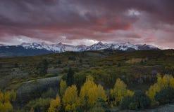 Το ηλιοβασίλεμα πέρα από τη σειρά βουνών του San Juan και το χρώμα πτώσης φθινοπώρου του Ντάλλας διαιρούν Ridgway, Κολοράντο στοκ φωτογραφίες