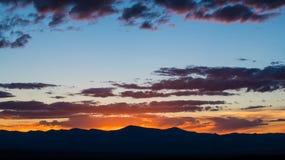 Το ηλιοβασίλεμα σκιαγραφεί μια σειρά βουνών και φωτίζει έναν δραματικό ουρανό βραδιού με τα πορφυρά και ρόδινα σύννεφα στοκ φωτογραφία με δικαίωμα ελεύθερης χρήσης