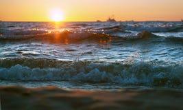 Το ηλιοβασίλεμα στη θάλασσα, τα κύματα κτύπησε ενάντια στον κυματοθραύστη, η θάλασσα στην αυγή, τα σκάφη στον ορίζοντα Στοκ φωτογραφία με δικαίωμα ελεύθερης χρήσης