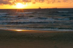 Το ηλιοβασίλεμα στη θάλασσα, τα κύματα κτύπησε ενάντια στον κυματοθραύστη, η θάλασσα στην αυγή, τα σκάφη στον ορίζοντα Στοκ Φωτογραφίες