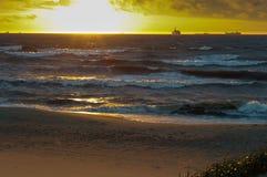 Το ηλιοβασίλεμα στη θάλασσα, τα κύματα κτύπησε ενάντια στον κυματοθραύστη, η θάλασσα στην αυγή, τα σκάφη στον ορίζοντα Στοκ εικόνες με δικαίωμα ελεύθερης χρήσης
