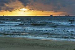 Το ηλιοβασίλεμα στη θάλασσα, τα κύματα κτύπησε ενάντια στον κυματοθραύστη, η θάλασσα στην αυγή, τα σκάφη στον ορίζοντα Στοκ Φωτογραφία