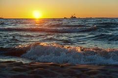 Το ηλιοβασίλεμα στη θάλασσα, τα κύματα κτύπησε ενάντια στον κυματοθραύστη, η θάλασσα στην αυγή, τα σκάφη στον ορίζοντα Στοκ Εικόνες