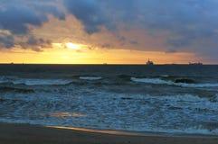 Το ηλιοβασίλεμα στη θάλασσα, τα κύματα κτύπησε ενάντια στον κυματοθραύστη, η θάλασσα στην αυγή, τα σκάφη στον ορίζοντα Στοκ εικόνα με δικαίωμα ελεύθερης χρήσης