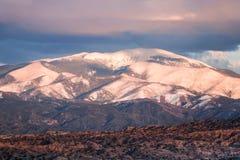 Το ηλιοβασίλεμα φωτίζει χιονοσκεπές Sangre de Cristo Mountains και τα ζωηρόχρωμα σύννεφα και badlands κοντά στη Σάντα Φε, Νέο Μεξ στοκ φωτογραφίες με δικαίωμα ελεύθερης χρήσης