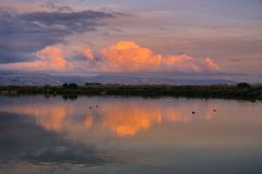 Το ηλιοβασίλεμα χρωμάτισε τα σύννεφα πέρα από τα βουνά Santa Cruz που απεικονίστηκαν στις λίμνες του κόλπου του νότιου Σαν Φρανσί Στοκ εικόνες με δικαίωμα ελεύθερης χρήσης