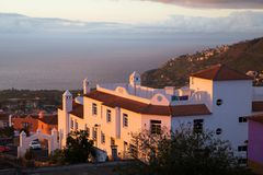 Το ηλιοβασίλεμα Tenerife, Ισπανία διαδίδει το μαλακό πορφυρό φως του στον ωκεανό, τα βουνά και τα σπίτια Στοκ εικόνα με δικαίωμα ελεύθερης χρήσης