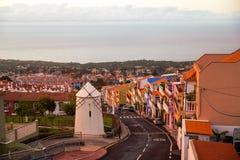 Το ηλιοβασίλεμα Tenerife, Ισπανία διαδίδει το μαλακό πορφυρό φως του στον ωκεανό, τα βουνά και τα σπίτια Στοκ Εικόνες