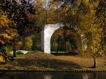 Το ηλιόλουστο φθινόπωρο με τα κίτρινα δέντρα και ένα τούβλο σχηματίζουν αψίδα στο πάρκο Tsaritsyno στη Μόσχα στοκ φωτογραφίες