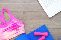 Το δημιουργικό επίπεδο βάζει των αθλητικών εξοπλισμών και του ιματισμού με το lap-top στο ξύλινο πάτωμα, ικανότητα και υγιής Στοκ Εικόνες