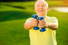Το ηλικιωμένο άτομο κρατά τους αλτήρες στοκ εικόνα με δικαίωμα ελεύθερης χρήσης