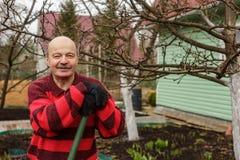 Το ηλικιωμένο άτομο με ένα εργαλείο κήπων στηρίζεται μετά από την εργασία Στοκ Εικόνες