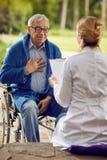 Το ηλικιωμένο άτομο στην αναπηρική καρέκλα που φορούν ` τ αισθάνεται καλό με τη νοσοκόμα Στοκ Εικόνες