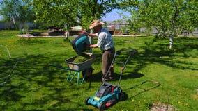 Το ηλικιωμένο άτομο τινάζει το καλάθι με τη χλόη περικοπών στο κάρρο Αργό MO φιλμ μικρού μήκους