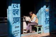 Το ηλικιωμένο ασιατικό άτομο διάβασε μια εφημερίδα στο ηλιόλουστο πρωί στοκ εικόνα με δικαίωμα ελεύθερης χρήσης