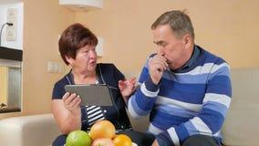 Το ηλικιωμένο ζεύγος λαμβάνει τις διαβουλεύσεις γιατρών για τα PC ταμπλετών Το άτομο βήχει και ο γιατρός δίνει τις συμβουλές για  φιλμ μικρού μήκους