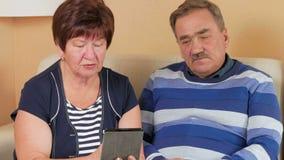 Το ηλικιωμένο ζεύγος λαμβάνει τις διαβουλεύσεις γιατρών για τα PC ταμπλετών Το άτομο βήχει και ο γιατρός δίνει τις συμβουλές για  απόθεμα βίντεο