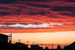 Το ηλιοβασίλεμα ανάβει επάνω τα σύννεφα επάνω από μια αστική οδό Στοκ Εικόνες