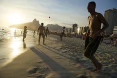 Το ηλιοβασίλεμα Nove Posto σκιαγραφεί το παίζοντας ποδόσφαιρο Ρίο παραλιών Altinho Στοκ Φωτογραφία