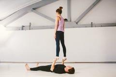Το θέμα είναι αθλητισμός και επιφάνεια Ένα νέα καυκάσια αρσενικό και ένα θηλυκό συνδέουν την ακροβατική γιόγκα άσκησης σε μια άσπ Στοκ εικόνα με δικαίωμα ελεύθερης χρήσης