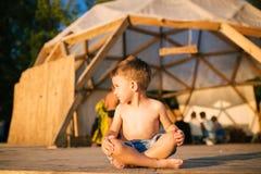 Το θέμα είναι γιόγκα και παιδιά Καυκάσιο παιδί αγοριών που κάθεται χωρίς παπούτσια cross-legged στη θέση λωτού στο ξύλινο πάτωμα Στοκ φωτογραφίες με δικαίωμα ελεύθερης χρήσης