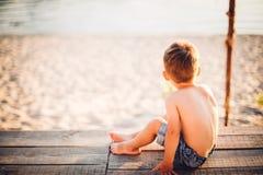 Το θέμα είναι διακοπές παραλιών παιδιών και καλοκαιριού Ένα μικρό αγόρι κάθεται με την πλάτη του σε μια ξύλινη αποβάθρα και θαυμά Στοκ Εικόνα