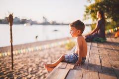 Το θέμα είναι διακοπές παραλιών παιδιών και καλοκαιριού Ένα μικρό αγόρι κάθεται λοξά σε μια ξύλινη αποβάθρα και θαυμάζει την άποψ Στοκ φωτογραφία με δικαίωμα ελεύθερης χρήσης