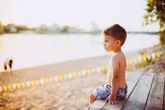 Το θέμα είναι διακοπές παραλιών παιδιών και καλοκαιριού Ένα μικρό αγόρι κάθεται λοξά σε μια ξύλινη αποβάθρα και θαυμάζει την άποψ Στοκ Εικόνες
