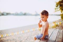 Το θέμα είναι διακοπές παραλιών παιδιών και καλοκαιριού Ένα μικρό αγόρι κάθεται λοξά σε μια ξύλινη αποβάθρα και θαυμάζει την άποψ Στοκ Φωτογραφίες