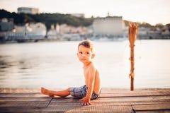 Το θέμα είναι διακοπές παραλιών παιδιών και καλοκαιριού Ένα μικρό καυκάσιο αγόρι κάθεται λοξά σε μια ξύλινη αποβάθρα και εξετάζει Στοκ Φωτογραφίες