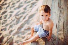 Το θέμα είναι διακοπές παραλιών παιδιών και καλοκαιριού Ένα μικρό καυκάσιο αγόρι κάθεται λοξά σε μια ξύλινη αποβάθρα και εξετάζει Στοκ φωτογραφίες με δικαίωμα ελεύθερης χρήσης
