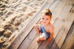 Το θέμα είναι διακοπές παραλιών παιδιών και καλοκαιριού Ένα μικρό καυκάσιο αγόρι κάθεται λοξά σε μια ξύλινη αποβάθρα και εξετάζει Στοκ Εικόνες