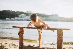 Το θέμα είναι διακοπές παραλιών παιδιών και καλοκαιριού Ένα μικρό καυκάσιο αγόρι αναρριχείται επάνω σε έναν ξύλινο πάγκο στην όχθ Στοκ Φωτογραφίες