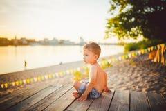 Το θέμα είναι διακοπές παραλιών παιδιών και καλοκαιριού Ένα μικρό καυκάσιο αγόρι κάθεται λοξά σε μια ξύλινη αποβάθρα και θαυμάζει Στοκ Φωτογραφίες
