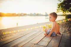Το θέμα είναι διακοπές παραλιών παιδιών και καλοκαιριού Ένα μικρό καυκάσιο αγόρι κάθεται λοξά σε μια ξύλινη αποβάθρα και θαυμάζει Στοκ Εικόνες